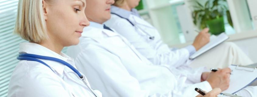 Foto von Ärzten, die auf Klemmbrettern schreiben