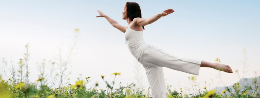 Bild einer weiß gekleideten, yogaausübenden Frau auf einer gelben Blumenwiese
