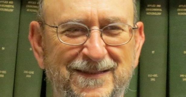 Portrait von Charles Gerbe vor einem Bücherregal mit grünen Büchern