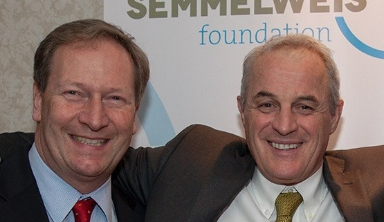 Picture of Bernhard Küenburg and Didier Pittet smiling in front of a poster with the Semmelweis Foundation logo on it