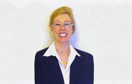 Portrait of Dr. Sharon L. Kurtz in a white shirt and dark blue jacket in front of a white wall