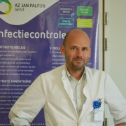 Portrait of Dr. Louis Ide in front of a poster of AZ Jan Palfijn in Gent